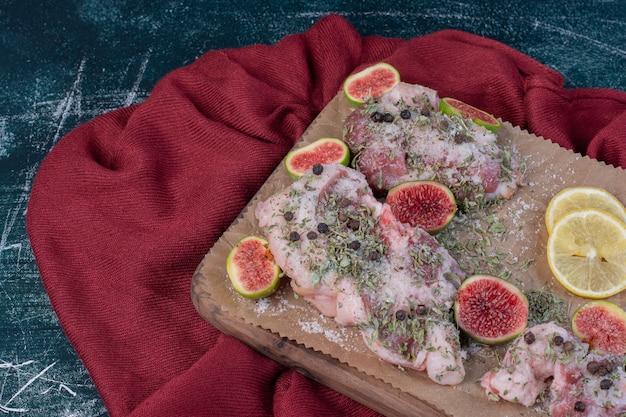 Costolette crude in tavola di legno con fichi, erbe secche e panno rosso. Foto Gratuite