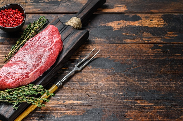 Сырой стейк rump, говядина. темный деревянный фон. вид сверху. скопируйте пространство. Premium Фотографии