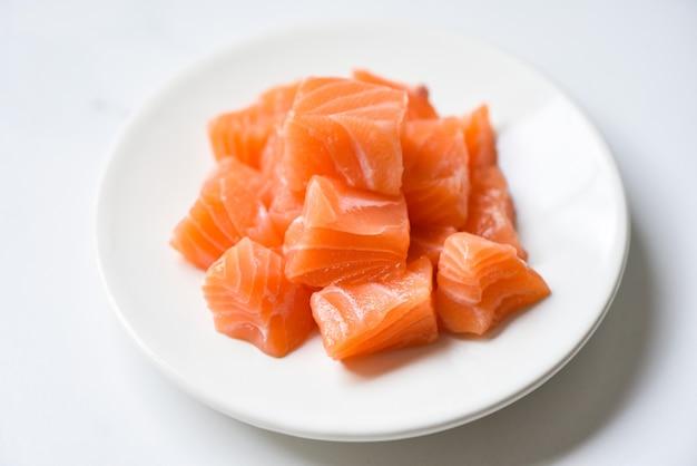 Кубик сырого филе лосося на белой тарелке и белом столе Premium Фотографии