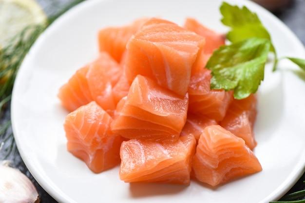Кубик сырого филе лосося с травами и специями / свежая лососевая рыба Premium Фотографии