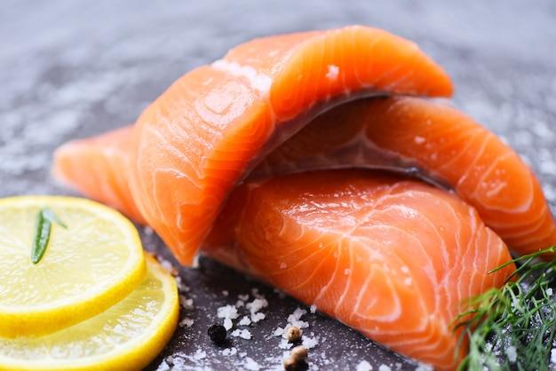 Сырое филе лосося с травами и специями розмарин пищевой лимон на черном Premium Фотографии