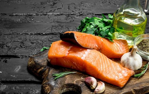 Стейки из сырой рыбы из лосося с травами и специями. на черном деревенском. Premium Фотографии