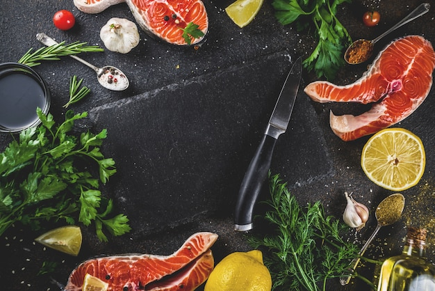 Raw salmon fish steaks with lemon, herbs, olive oil, ready for grill Premium Photo