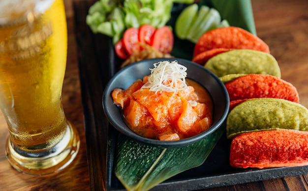 생 연어 매운 샐러드는 카나페와 시원한 맥주를 위해 빨강 및 녹색 바삭 바삭한 칩과 함께 제공됩니다. 프리미엄 사진