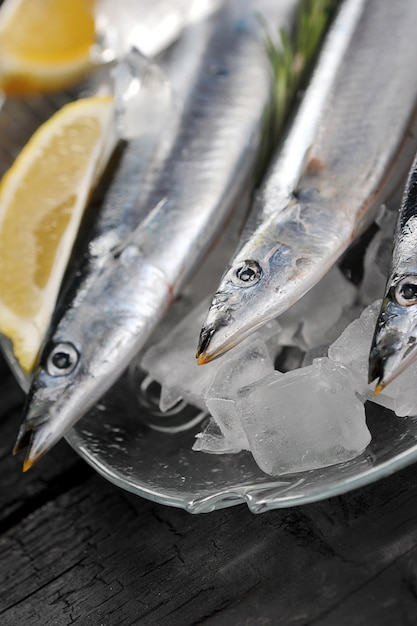 Raw saury on a glass dish in the form of fish with rosemary and lemon Premium Photo