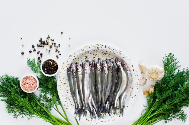 Raw smelt on a plate, dill, pink salt, pepper and garlic. Premium Photo