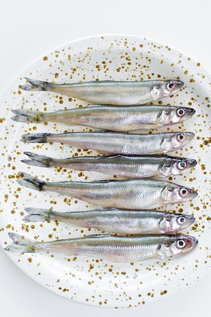 Raw smelt on a plate. Premium Photo