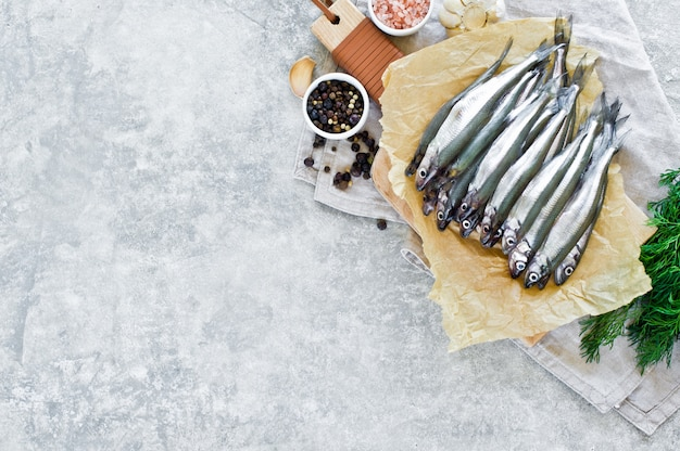 Raw smelt on a wooden chopping board, dill, pink salt, pepper and garlic. Premium Photo