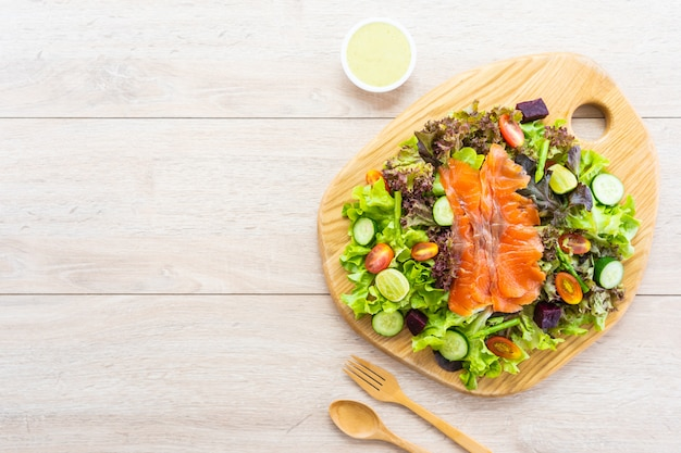 Raw smoked salmon meat fish with fresh green vegetable salad Free Photo