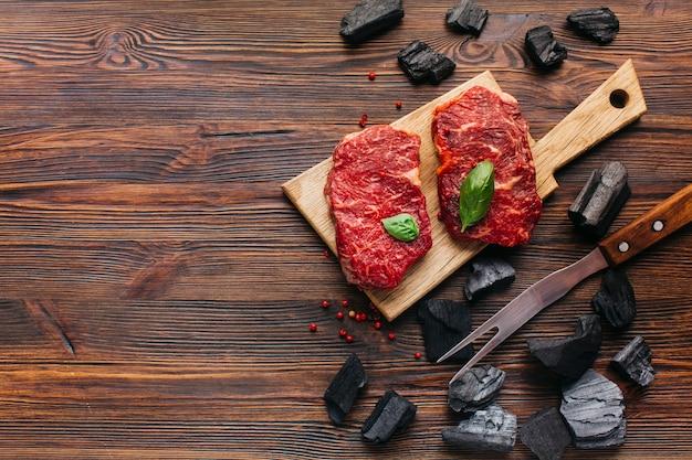 木の織り目加工の背景上の石炭とバーベキューフォークでまな板の上の生ステーキ 無料写真