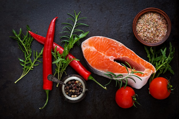 Raw steak salmon and vegetables for cooking on a black table.  top view Free Photo