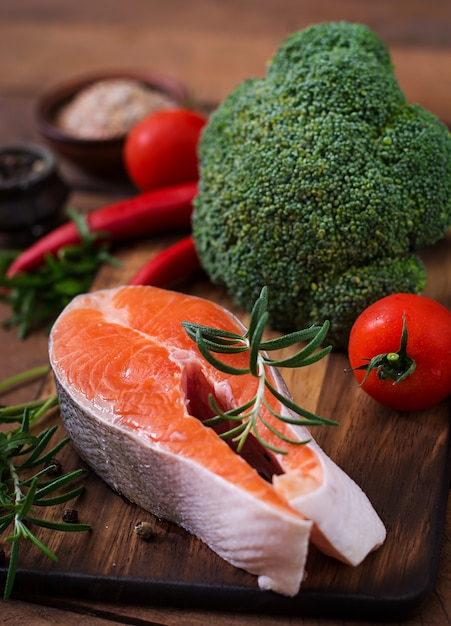 Raw steak salmon and vegetables for cooking on wooden table in a rustic style. Free Photo