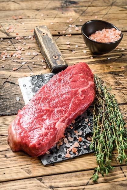 Сырой стейк из стриплойна на мясорубке, мраморная говядина. деревянный фон. вид сверху. Premium Фотографии
