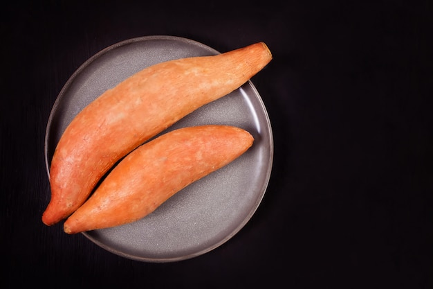 Raw sweet potatoes on the black surface. top view. Premium Photo