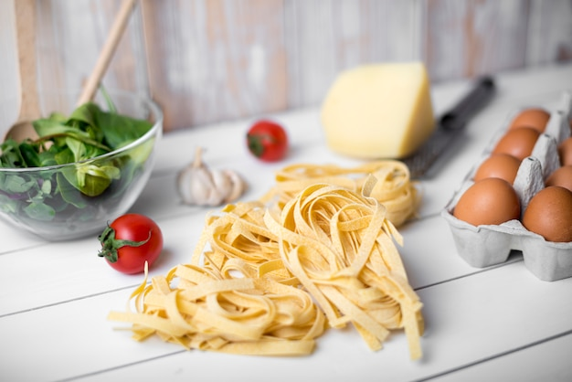 Raw tagliatelle pasta and ingredient over wooden table Free Photo
