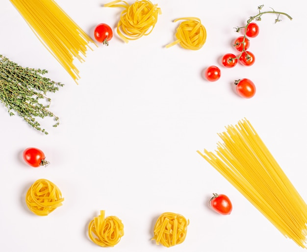 Raw tagliatelle pasta, spaghetti with tomatoes, thyme, round frame with copy space for texat, flat lay. Premium Photo