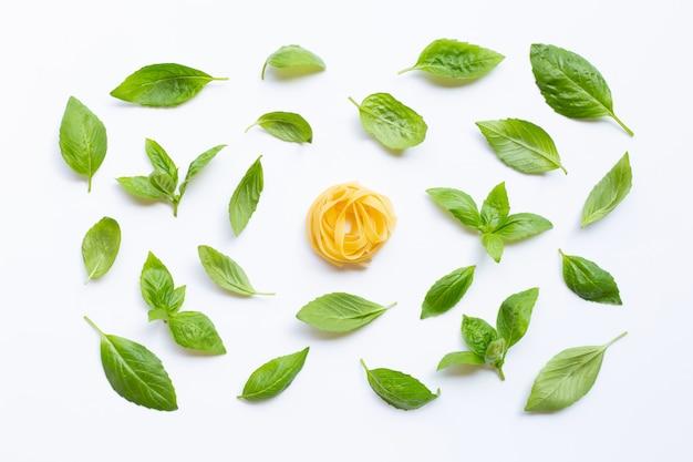 Raw tagliatelle pasta with basil leaves on white Premium Photo