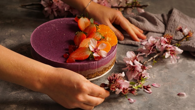 Raw vegan cake with fruit and seeds, decorated with flowers Premium Photo