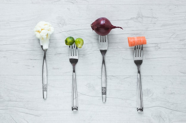 Raw vegetables on fork arranged in a row on wooden table Free Photo