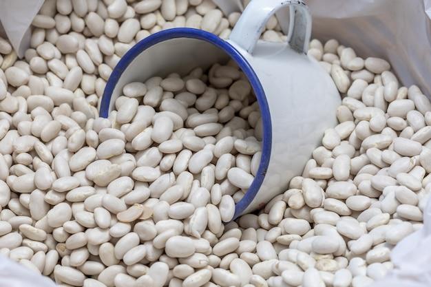 Raw white beans in bulk (sale of legumes) Premium Photo