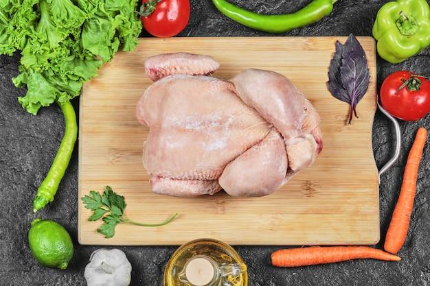 양상추, 고추, 기름, 토마토와 나무 보드에 원시 전체 치킨 무료 사진