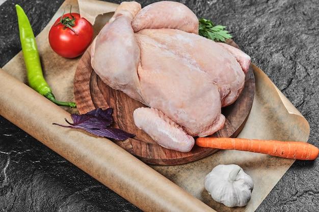 신선한 야채와 함께 나무 접시에 원시 전체 치킨 무료 사진