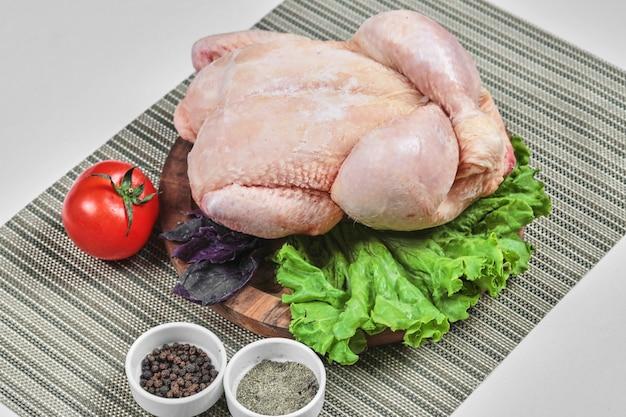 양상추, 토마토, 향신료와 나무 접시에 원시 전체 치킨 무료 사진
