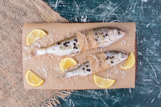 木の板にレモンスライス、コショウの粒、塩を入れた生の丸ごとの魚。 無料写真