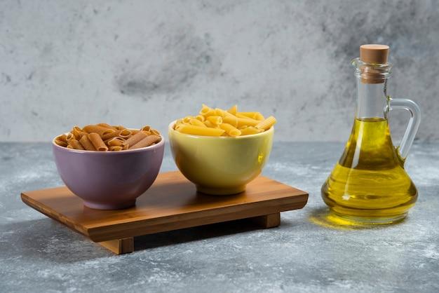 生の黄色と茶色のセモリナパスタとガラス瓶のオイル。 無料写真
