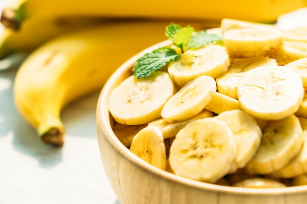 Raw yellow banana slices in wooden bowl Free Photo