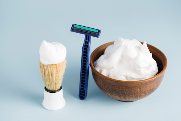 Razor; shaving brush and bowl of foam against blue backdrop Free Photo