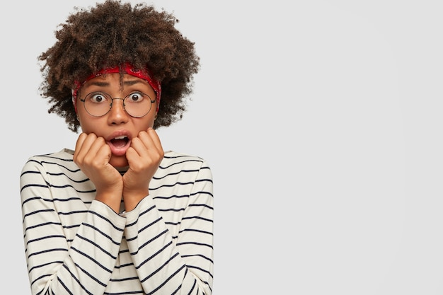 Reaction and emotions concept. stressful embrarrassed scared woman stares with widely opened eyes through spectacles Free Photo