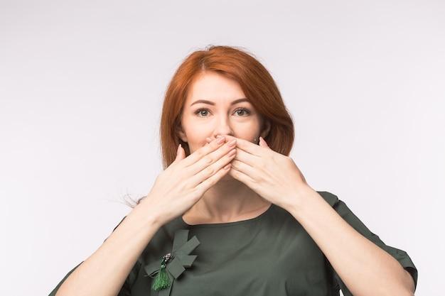 白い背景の上の口に手のひらを持つリードヘッドの女性 Premium写真