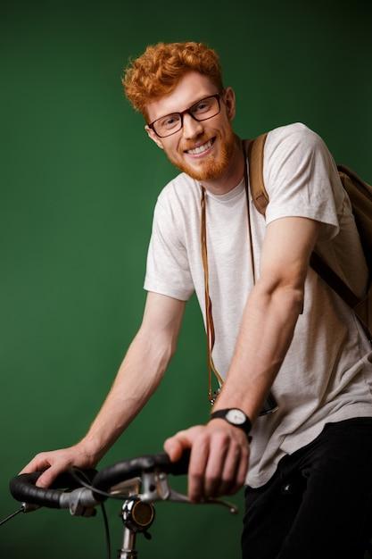 Молодой веселый readhead бородатый битник с рюкзаком и ретро-камерой, готовый ездить на велосипеде Бесплатные Фотографии
