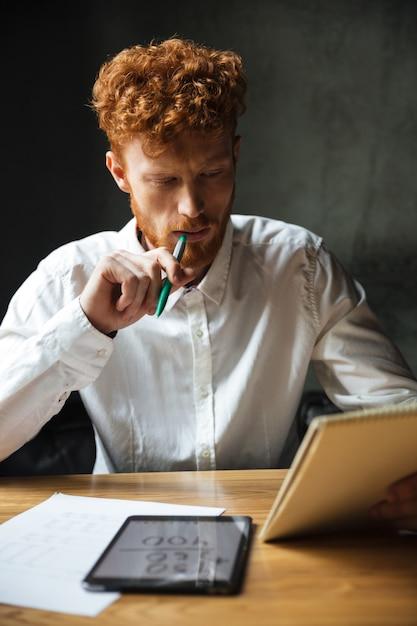 Фотография молодого мыслящего readhead бородатого мужчины в белой рубашке, читающего заметки, сидящего за деревянным столом Бесплатные Фотографии