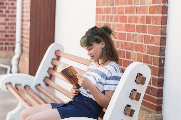 ベンチに座っている読書少女 無料写真