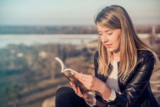 Reading her favorite book. Beautiful young woman reading book and smiling while sitting outdoors,  landscape on the background. Reading a book concept Free Photo