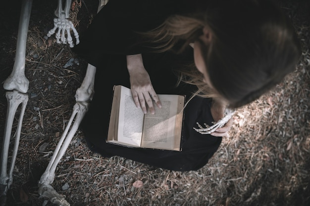 Reading lady in dark clothes nearbones Free Photo