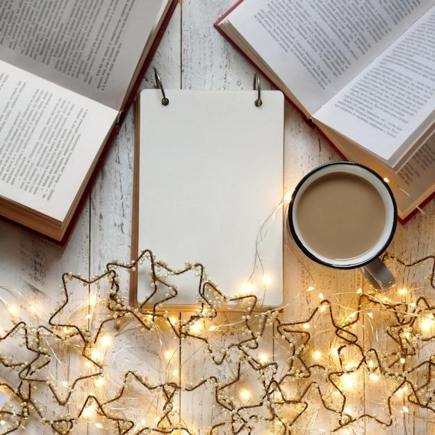 冬の本。冬の居心地の良いreading.toは、冬休みにリストを行います。紅茶と明るい花輪の買い物リスト。冬。 christmas.blankメモ帳と明るいガーランドの計画 Premium写真