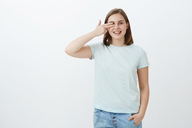 Leggere le parole con un occhio solo nel negozio di ottica, raccogliendo nuovi occhiali. ritratto di donna affascinante gioiosa dall'aspetto amichevole con capelli castani corti che tengono le dita a vista che puntano a destra e sorridono gioiosamente Foto Gratuite
