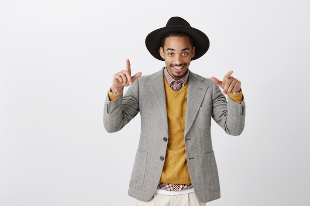 Ready to chill at sassy party. portrait of wealthy good-looking african-american in stylish outfit and round hat, making cool gestures while dancing or hanging out with friends over gray wall Free Photo