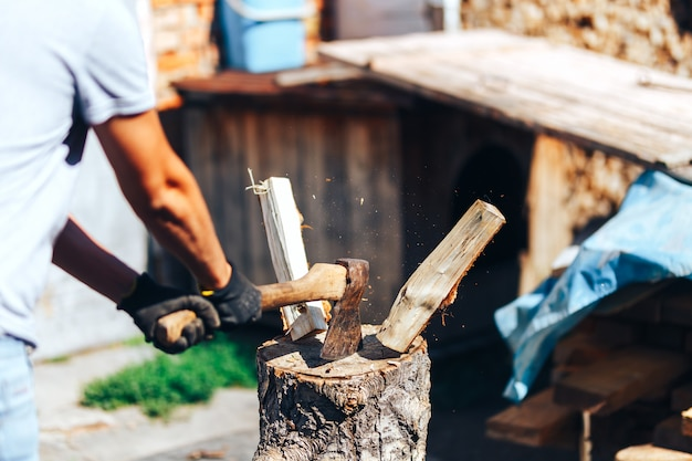 Ready for cutting timber. close-up of axe cutting log while other logs laying in the background Premium Photo