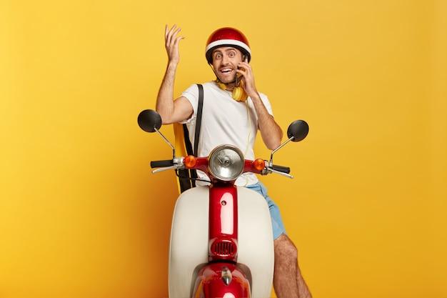 Pronto a partire. il pilota maschio confuso felice si siede sullo scooter, ha una conversazione telefonica mentre si ferma sulla strada, tiene il braccio alzato, trasporta un piccolo zaino, indossa il casco protettivo, lavora nel servizio di consegna Foto Gratuite