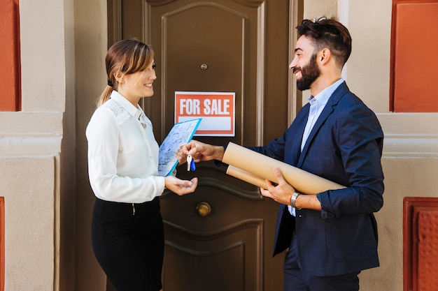 Real estate agent and business woman interchanging keys Free Photo