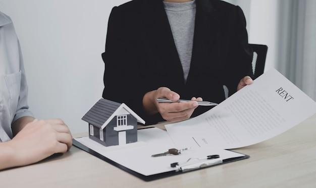 Рука агента по недвижимости, держащая ручку, указывает на деловой договор, аренду, покупку, ипотеку, ссуду, страхование жилья. Premium Фотографии