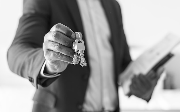 Real estate agent handing the house key Free Photo