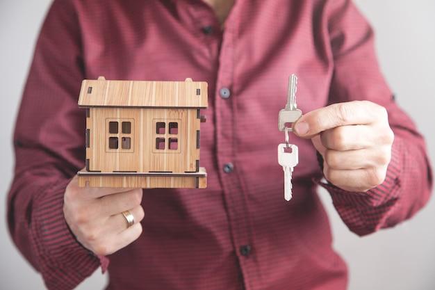 Агент по недвижимости держит ключи от дома с моделью дома в офисе бизнес-концепция Premium Фотографии