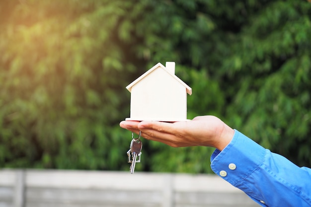 Real estate agent holding keys and house miniature Premium Photo
