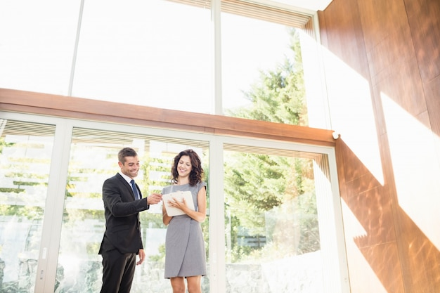Real-estate agent interacting with young woman showing new home Premium Photo
