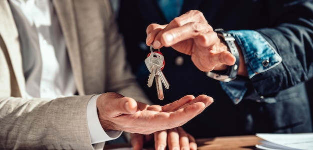 Real estate agent passing apartment keys to a client Premium Photo
